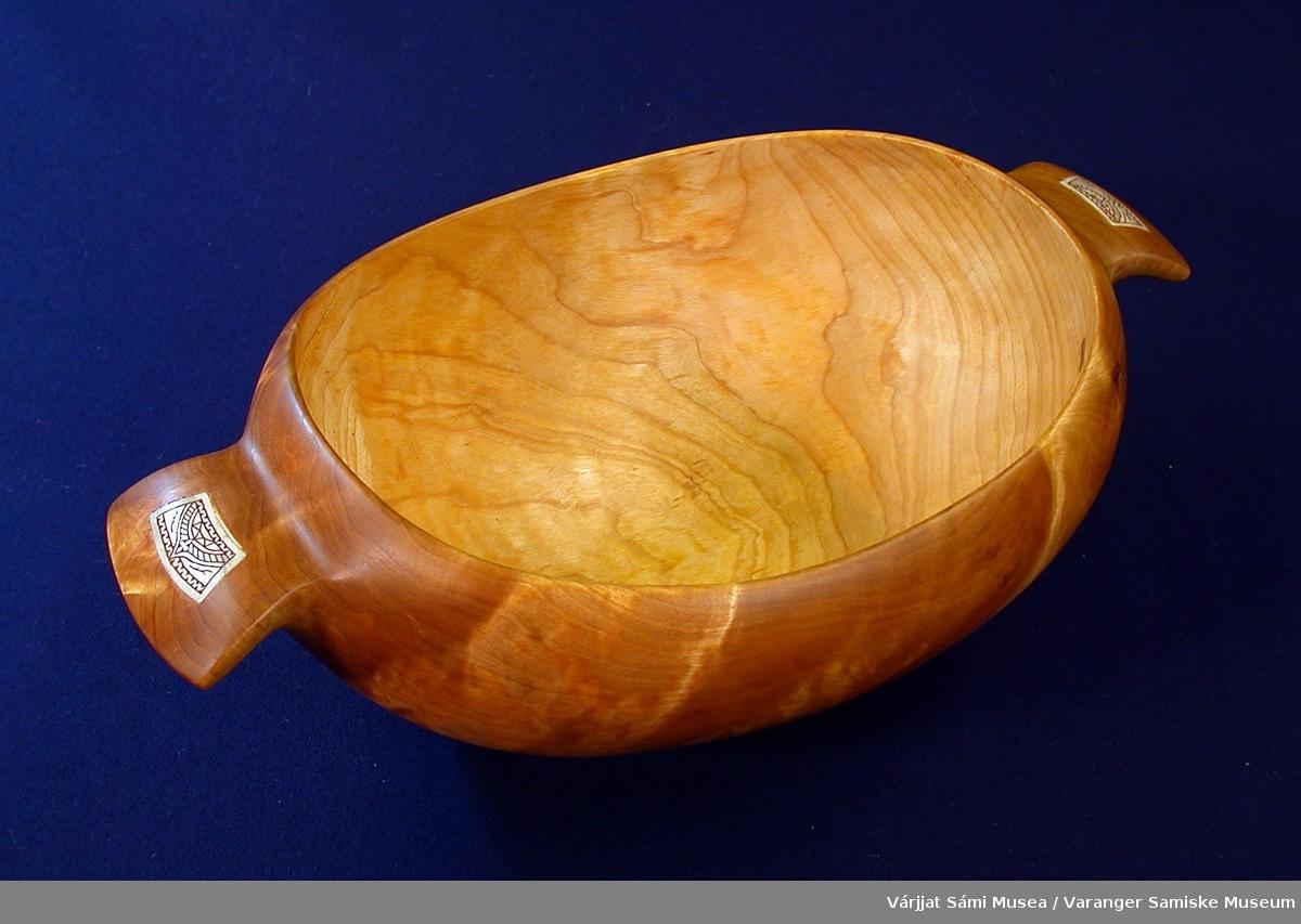 """Oval skål av bjørkerikule med innfelte horndetaljer. Skåla er oval med et håndtak i hver """"kortvegg"""". I håndtakene er det innfelt et avlangt, trapésformet hornstykke som er gravert og smurt med et fargestoff. Lengde fra innerkant itl innerkant er ca. 20 cm."""