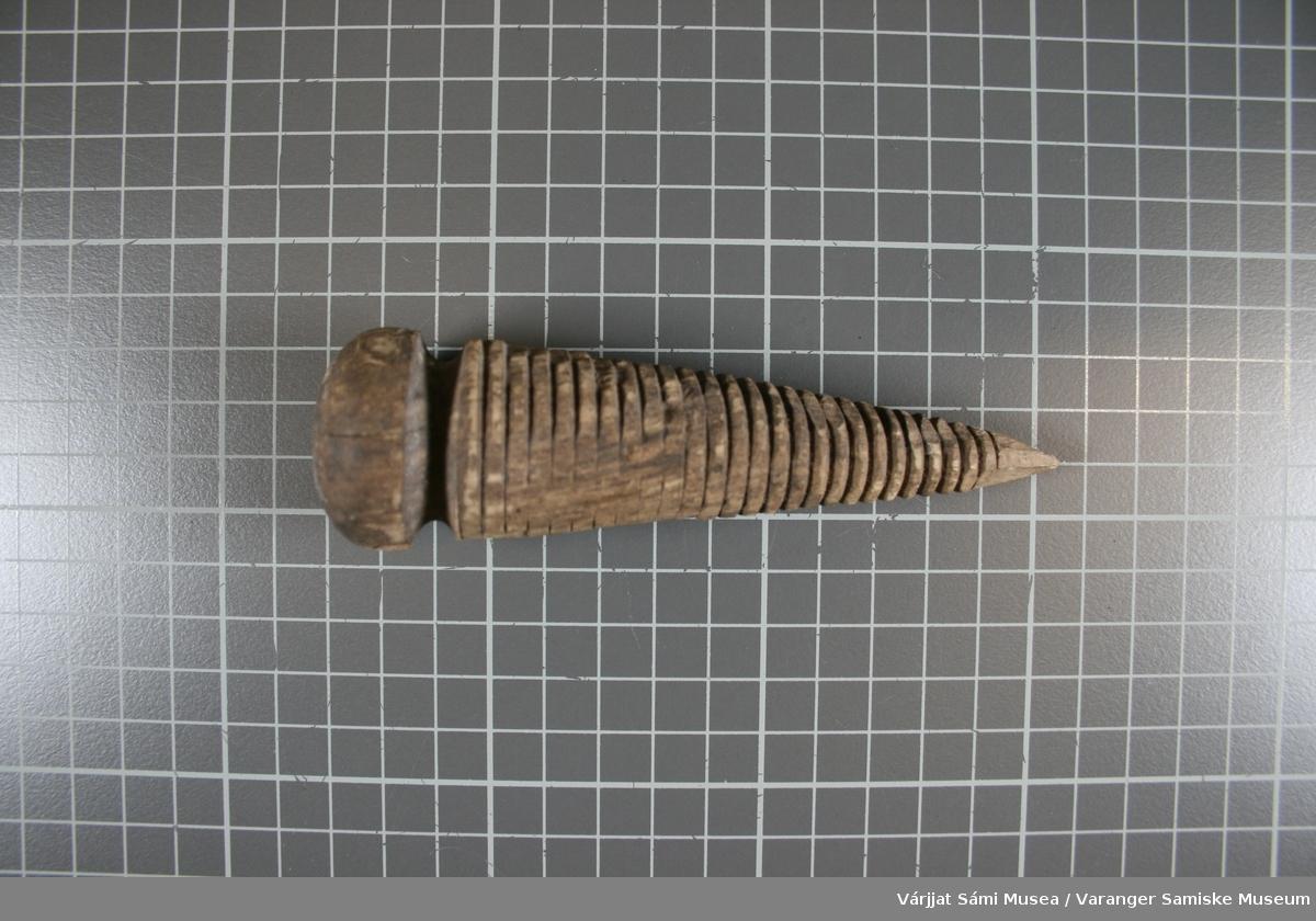 En kjegleformet gjenstand laget av bøk eller eik. Øverste del er dreid i benk, nederste del er spikket grovt og gjengene er laget med maskin.