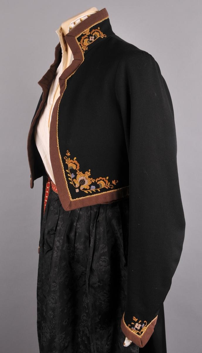 Stakk, liv, forkle, trøye, skjorte og tulleplagg. Stakk, liv er av svart ulldrapè og trøye  av svart ullgeorgette., kanta med  brunraudt klede. Alle delar har rosesaum.  Forkle i svart silkerips med flokktrykk, og med påsauma grindvove forkleband i ubleika lin og raudt og grønt ullgarn.  Skjorte i bomull med linningar i brun, ljosfiolett, grøn, beige og okerfarga rosesaum.  Svart tulleplagg av ull, montera, ferdig oppsett.