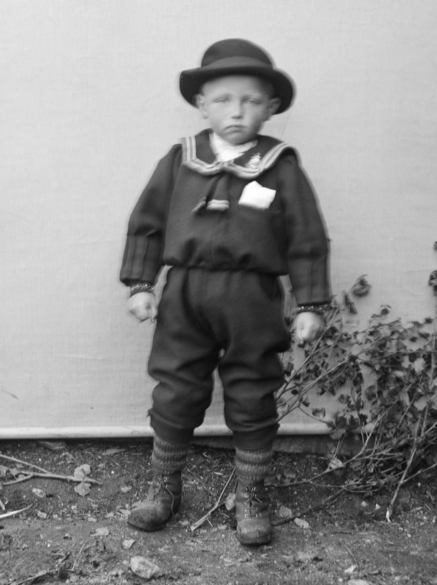 Gutt kledd i matrosdress og hatt, stående foran lerret