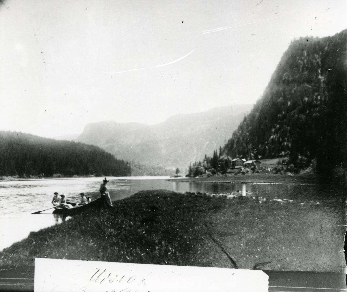 Trolig avbilding av fotografi. Fire kvinner i båt inntil land ved elv eller innsjø. Gård og bratt åskam i bakgrunnen