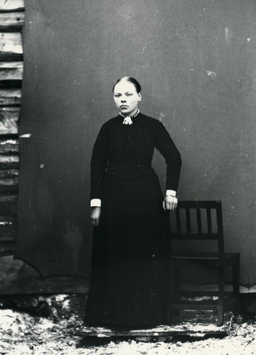 Kvinne i helfigur, stående ved stol, lerret festet på tømmervegg