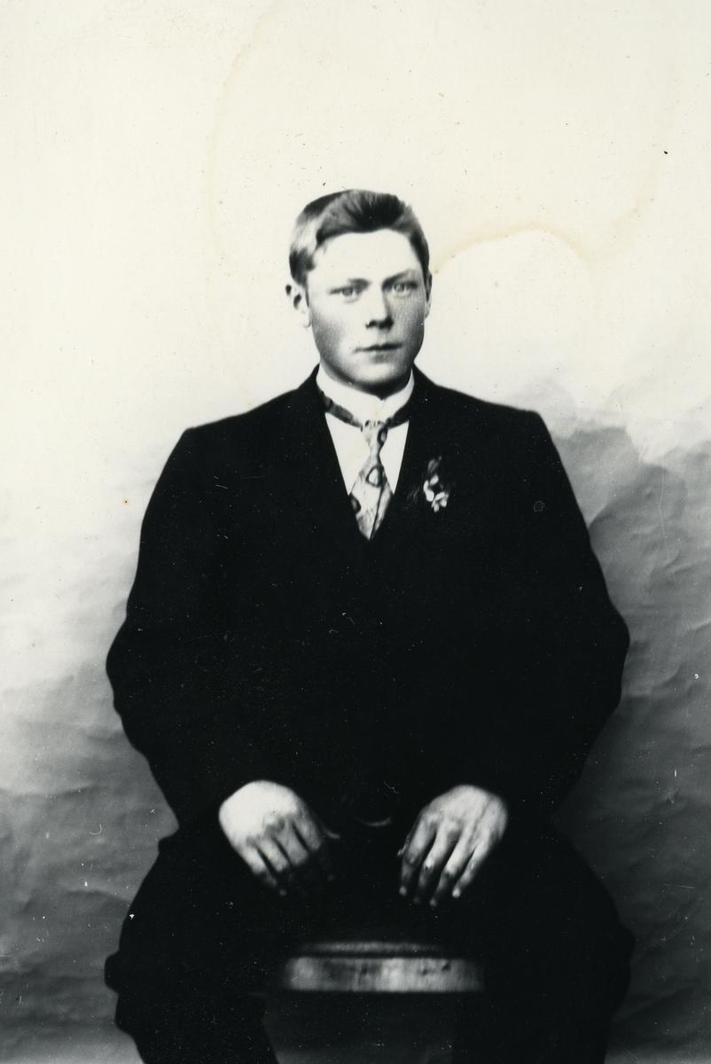 Ung dresskledd mann, sittende foran lerret