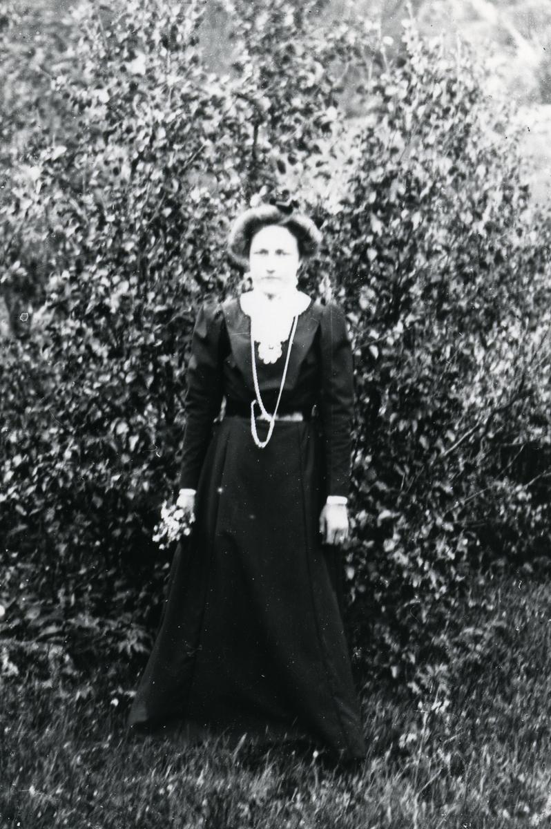 Kvinne i helfigur, foran busk