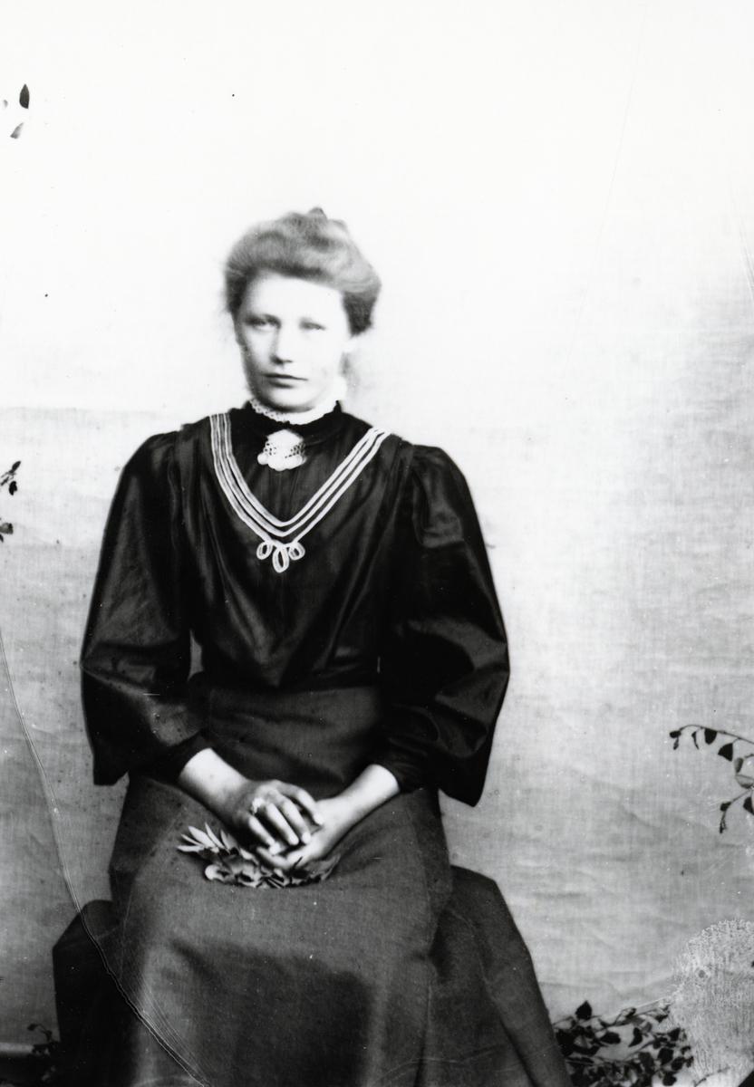 Kvinne i mørk bluse og skjørt, sittende foran lerret