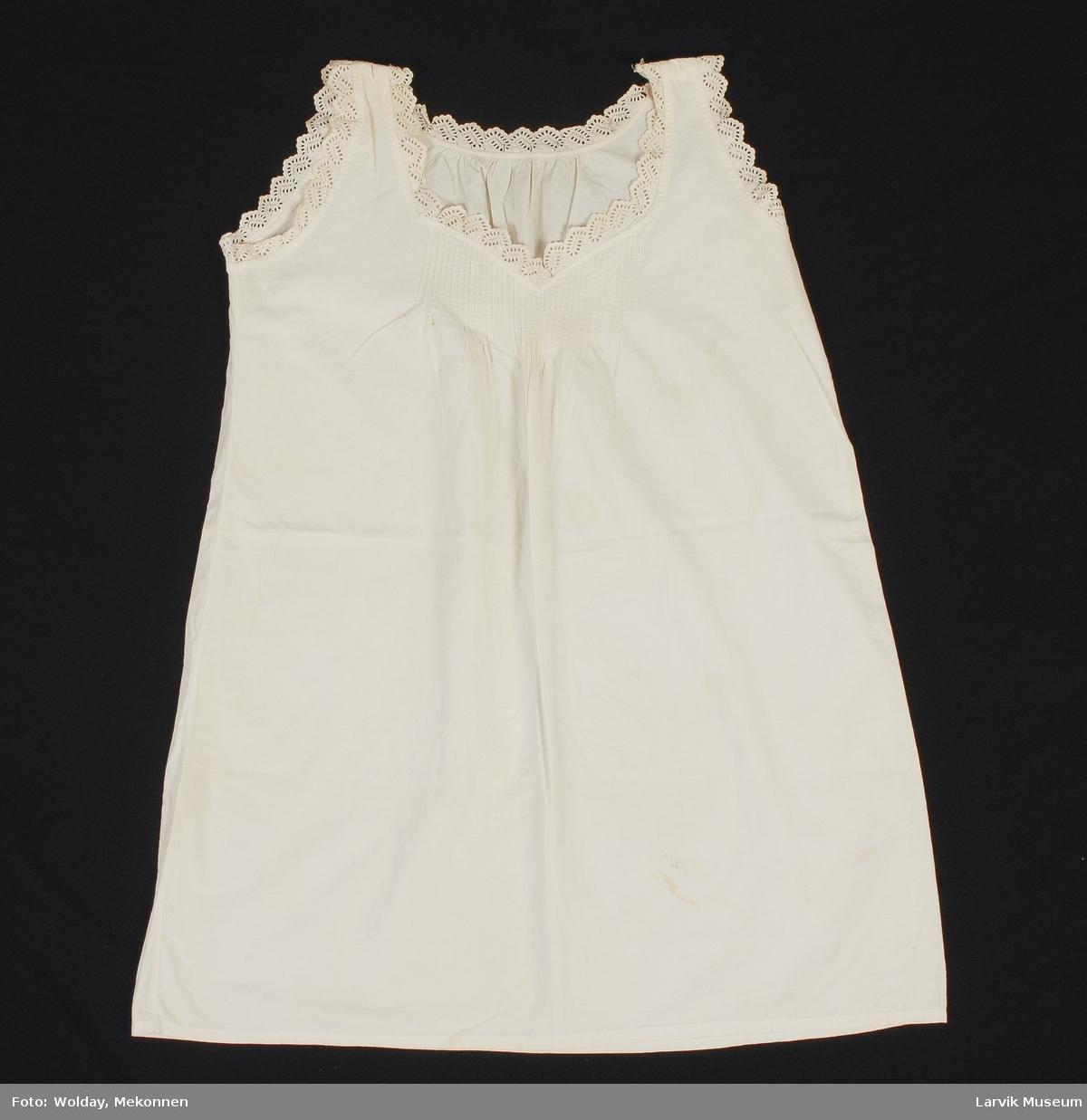 """Form: Kort """"kjole"""" med engelsk blonde i halslinning og ermlinning. Legg vertikalt et lite stykke foran.  Tidligere var det knepping over skuldrene, med disse er sydd igjen."""