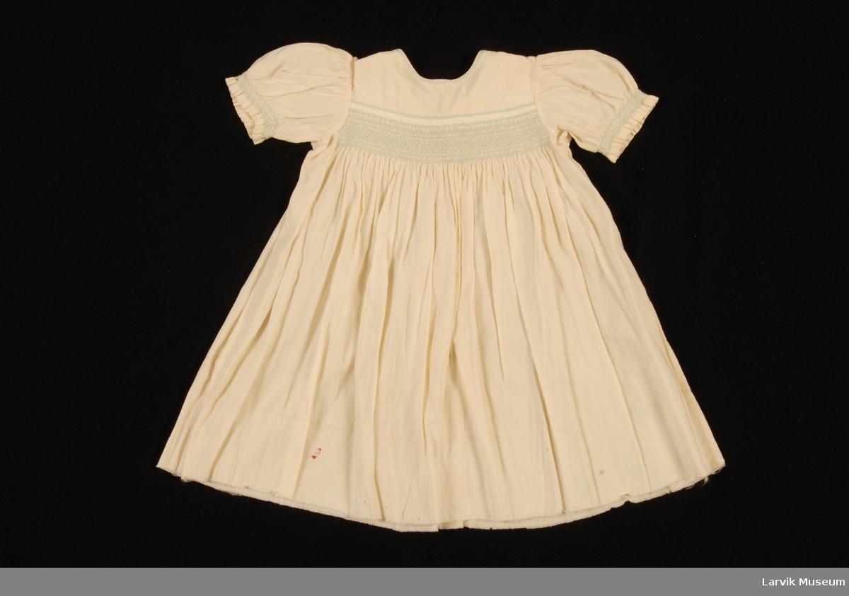 Form: Liten barnekjole med vaffelsøm på brystet og nederst på de korte ermene. Brodert i samme farge rundt halsen.5 perlemors knapper bak for lukking.