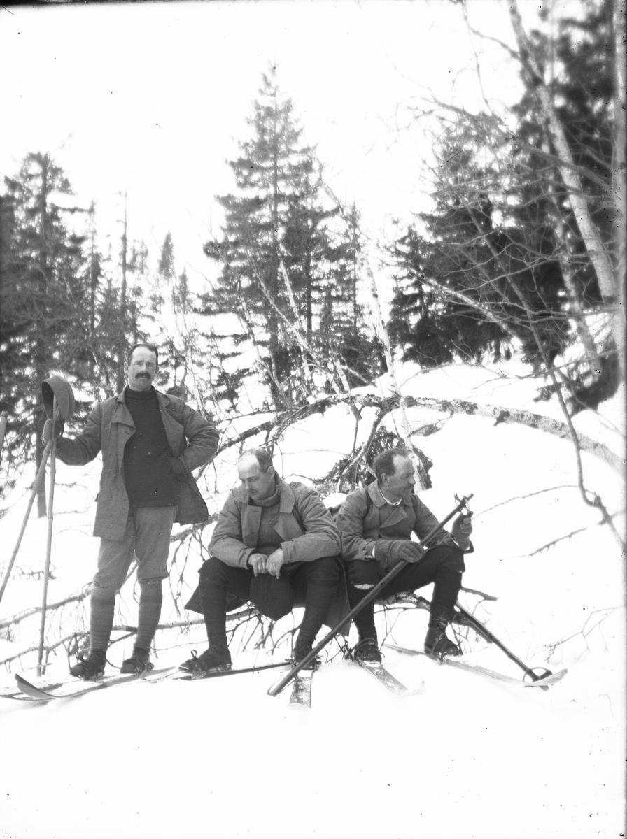 Tre menn på skitur, rast i skogen