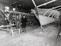 H. Berg-Olsens båtbyggeri: To menn foran to båter under bygg