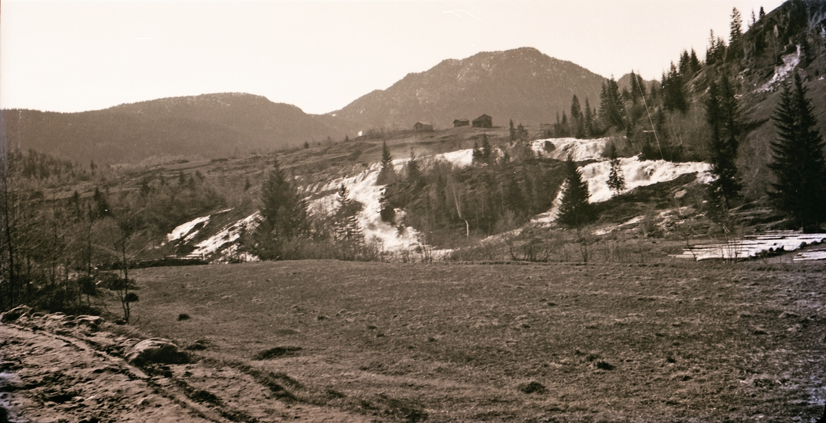 Tømmer på jorde, gård og høyt fjell i bakgrunnen