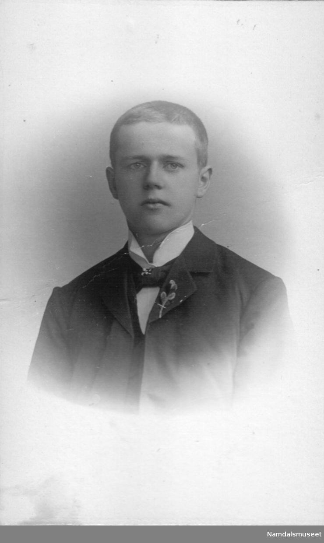 Portrett av en ung mann med blomst i jakkeslaget.