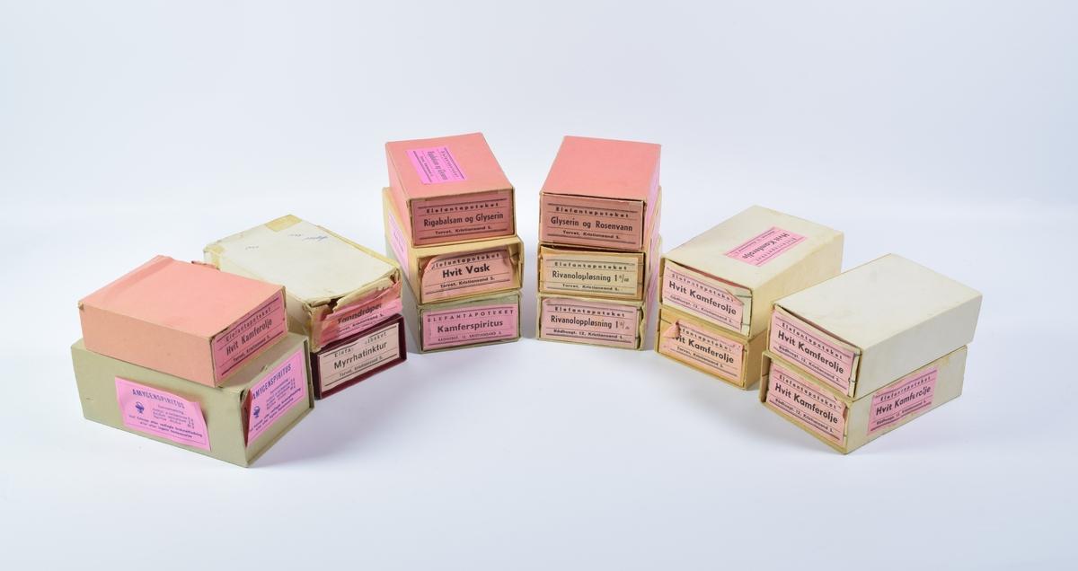 """15 esker med rektangulære, rosa etiketter for diverse medikamenter. Eskene består av to separate deler, hvor den ene ligger inne i den andre og kan skyves ut. De innerste eskene er stiftet sammen i hjørnene. Et eksemplar av hver etikett er limt på en av kortsidene og en eller to andre sider på hver eske.  Eske a er grå og inneholder etiketter for """"Amucenspiritus"""" Etikettene har blå skrift og et Hygiea-beger på venstre side.  Fem esker (b, c, d, e og f) inneholder etiketter for """"Hvit Kamferolje"""". Tre av eskene er hvite (b, c og d), en er brun (e) og en er rosa (f).  Eske g er rød og inneholder etiketter for """"Myrrhatinktur"""".  To esker, en brun (h) og en hvit (i) inneholder etiketter for """"Rivanoloppløsning 1‰"""".  Eske j er brun og inneholder etiketter for """"Hvit Vask"""".  Eske k er grå og inneholder etiketter for """"Kamferspiritus"""".  Eske l er hvit og inneholder etiketter for """"Tanndråper"""".  Eske m er rosa og inneholder etiketter for """"Rigabalsam og Glyserin"""".  Eske n er rosa og inneholder etiketter for """"Glyserin og Rosevann""""."""
