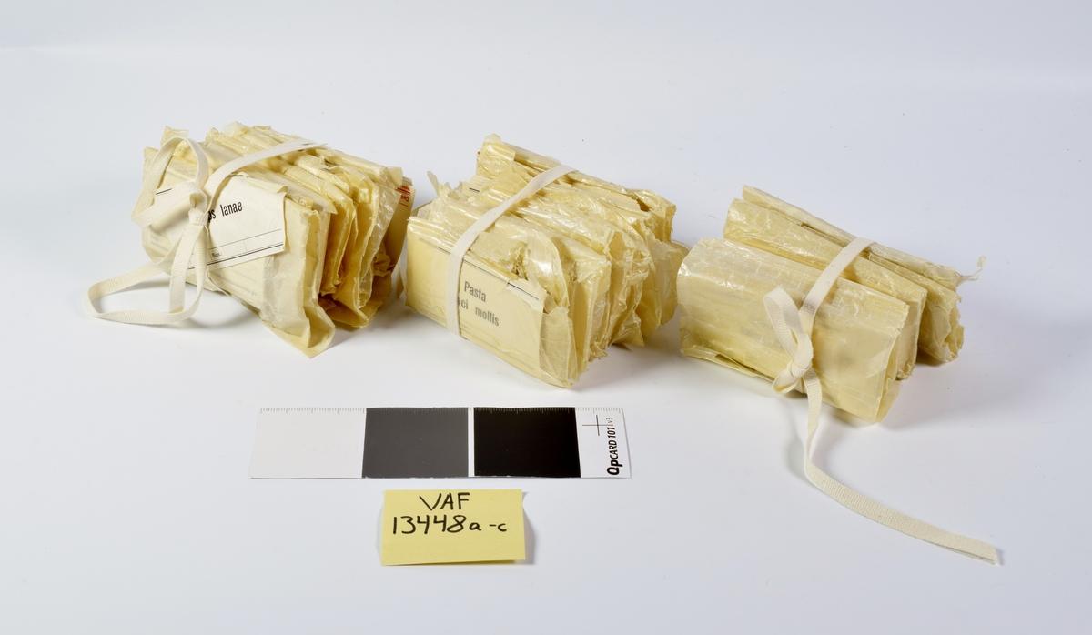 27 små pakker med farmasøytiske etiketter. Etikettene er hvite med sort skrift og en enkel bord øverst og nederst. Pakkene er ordnet i tre bunter.  Bunt a inneholder etiketter for: Sebum salicylatum Pasta zinc-lannani Pasta zinci Unguentum pomadinum Unguentum zinci comp. Unguentum lanolini boratum Vaselinum boricum  Bunt b inneholder etiketter for: Pasta zinci molliss Adeps lanae cum aqua Sebum bonzoatum Cremor ad manus Unguentum zinci oxidi Unguentum adipis suillus comp. Unguentum benzoes comp. Unguentum cerae boraxatum Unguentum camphoratum Unguentumbasilicm nigrum  Bunt c inneholder etiketter for: Adeps lanae Axungia benzoata Pasta salicylata Unguentum lannani Unguentum calcii carbonatis Unguentum zinc-lannani Unguentum acidi salicylici 50% NAF. 52 Unguentum amido-hydrargyricum (kors og rød skrift) Unguentum jecoris aselli