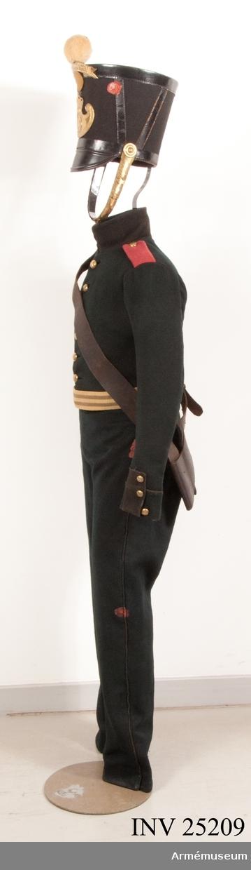 Grupp C I. Ur uniform för manskap vid Värmlands fältjägarkår (Värmlands fältjägarregemente), 1838-1845. Livplagg m/1838. Består av jacka, byxa, tschakå, pompon, kokard, namnplåt, vapenplåt, skor, damasker, skärp, patronkök, halsduk, bandolärrem, axelgehäng, sabelbajonettbalja. Jacka av mörkgrönt kläde med röda axelklaffar enkelknäppt med 7 kullriga mässingsknappar försedda med Värmlands reg:s nr 26, och fodrad med mörkgrönt ylletyg. Generalorder 1/12 1835, Värml. fältj. och 4/6 1838, inf allm.