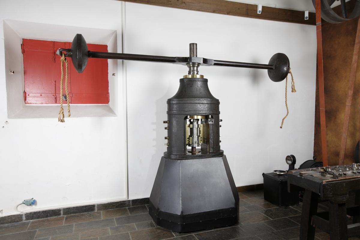 Pressen står på en sokkel. En vertikal metallsylinder er festet til midten av en svingarm. Armen har runde skiver i hver ytterkant.