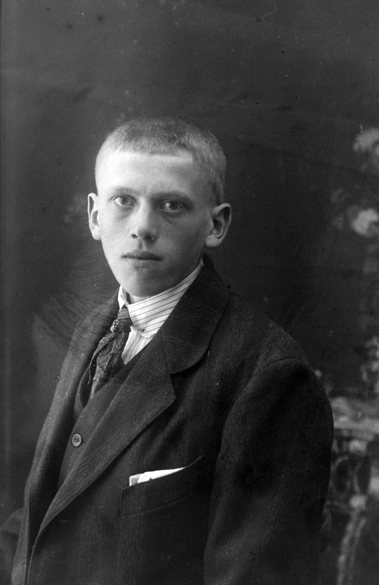 Studioportrett i halvfigur av en ung mann.