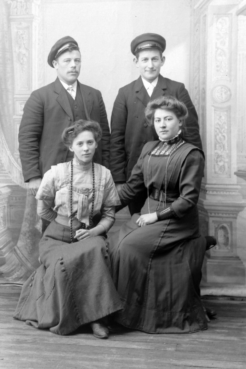 Studioportrett av fire personer i helfigur.