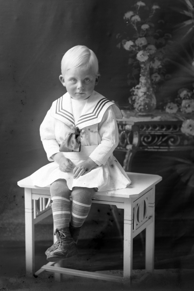 Studioportrett av et lite barn i helfigur, muligens Ivar Jacobsen.