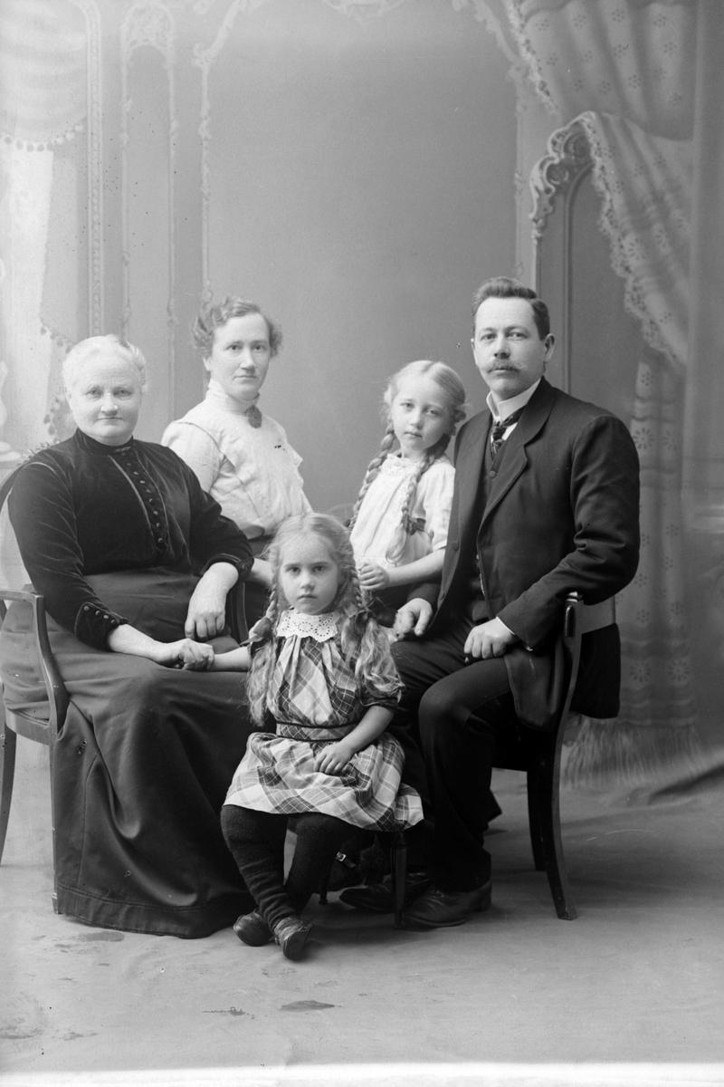 Studioportrett av en eldre kvinne med en mann, en kvinne og to barn.