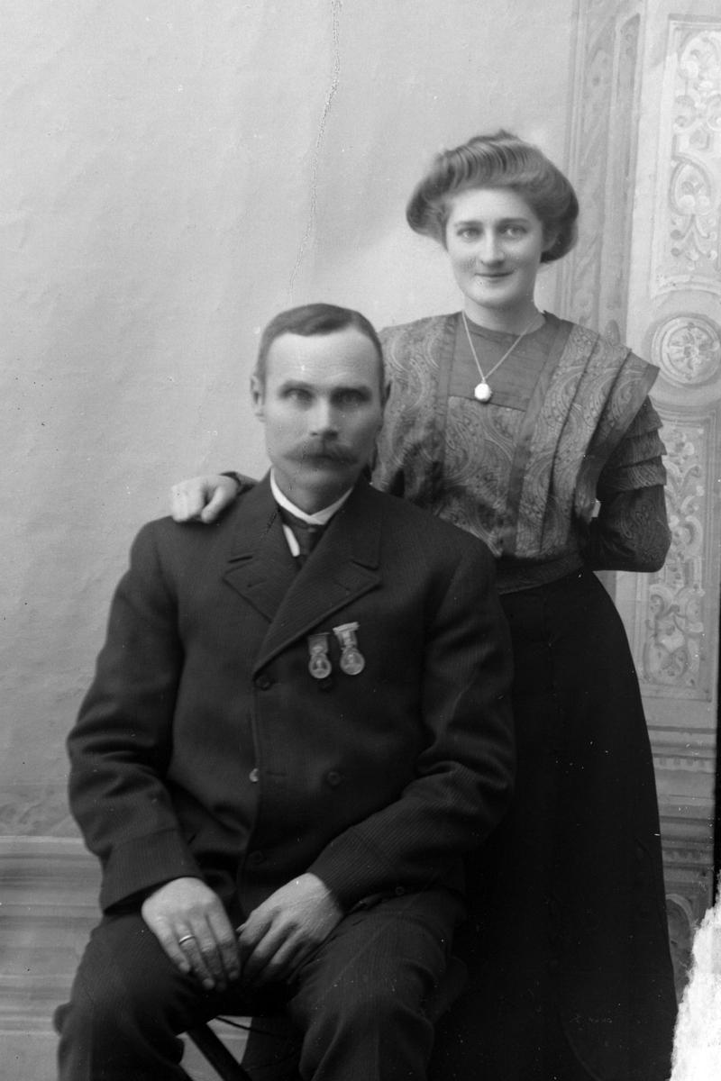 Studioportrett av en mann som sitter foran en stående kvinne.