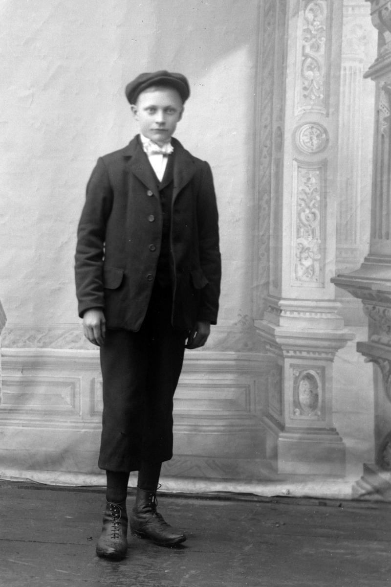 Studioportrett av en gutt med hatt.