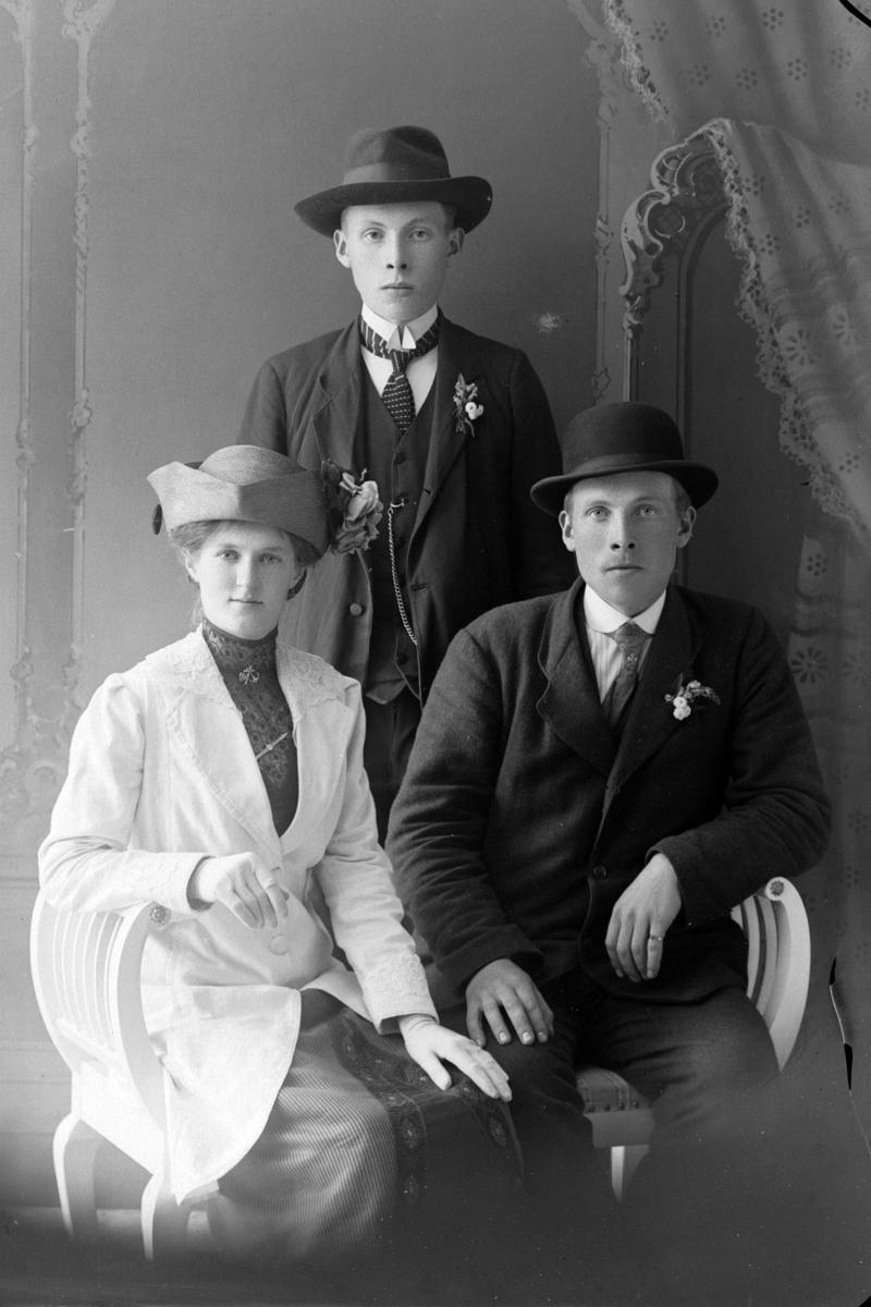 Studioportrett av en mann og kvinne som sitter, med en ung mann i bakgrunnen.