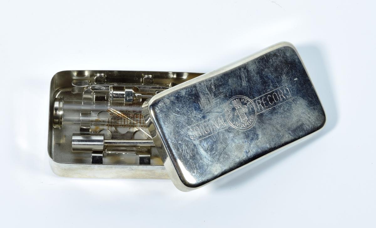 """Rektangulær metalleske som inneholder sprøyte. Esken består av bunn og lokk i sølvfarget metall. Bunnen er helt uten stempel/merker. På lokket er det trykt inn tekst og logo i metallet. I esken ligger det en sprøyte i glass med metalldeler i hver ende. På sprøyten er det millimetermål, samme logo som på eskens lokk og følgende tekst """"INSULIN-EINHEITEN"""". I esken ligger det et separat stempel og to sprøytespisser, alt i metall. Spissene er merket """"1"""". I tillegg ligger den en liten metallstand der med uviss funksjon Esken ligger i en plastpose som kan lukkes. På posen er det festet en etikett med tekst på tysk. Innholdet i esken ser komplett og ubrukt ut."""