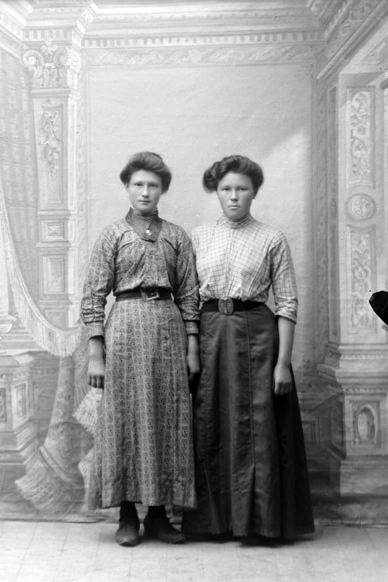 Studioportrett i helfigur av to kvinner.
