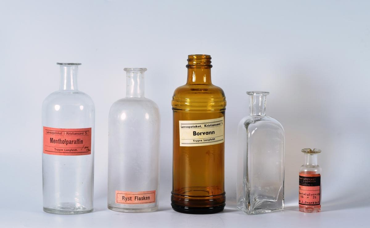 """Fem tomme glassflasker i ulike fasonger og størrelser.  a) rund glassflaske i klart glass. I bunnen av flaska står det """"250"""". Rundt flaska er det festa en rosa etikett med tekst/trykk i svart. Det er noen få bobler i glasset. Den har ingen kork.   b) rund glassflaske i klart glass. I bunnen av flaska står det """"250"""". Innvendig er det en del rester av noe hvitt. Kanten øverst på flaska er ujevn og mye bredere på den ene sida- Rundt flaska helt nederst er det festet en rosa etikett med trykk/tekst i svart. Flaska har ingen kork.   c) rund glassflaske i brunt glass. Den har gatte border/riller i glasset øverst og nederst. I bunnen av flaska står det """"566"""" (antageligvis). Rundt flaska er det festet en gulnet etikett med trykk/tekst i svart. Inni flaska ligger det en bit kork.  d) trekanta glassflaske i klart glass. Bunnen på flaska er tykkere midt på hver side av flaska enn den er i hjørnene. Den har ingen kork og/eller etiketter. Ingen merker i bunnen.   e) en liten flaske i klart glass. Den har helletut og ingen kork. Rundt flaska er det festet en rosa etikett med svart tekst/trykk fra Elefantapoteket med henvisning til pasient (datert 1941). I bunnen av flaska står det """"15""""."""