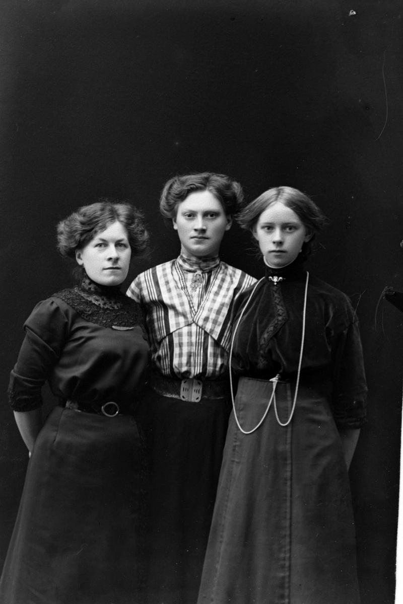 Studioportrett av tre kvinner foran en mørk bakgrunn.
