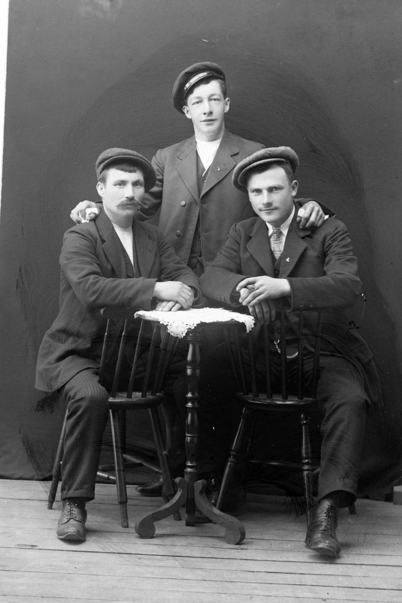 Studioportrett av tre menn rundt et bord.