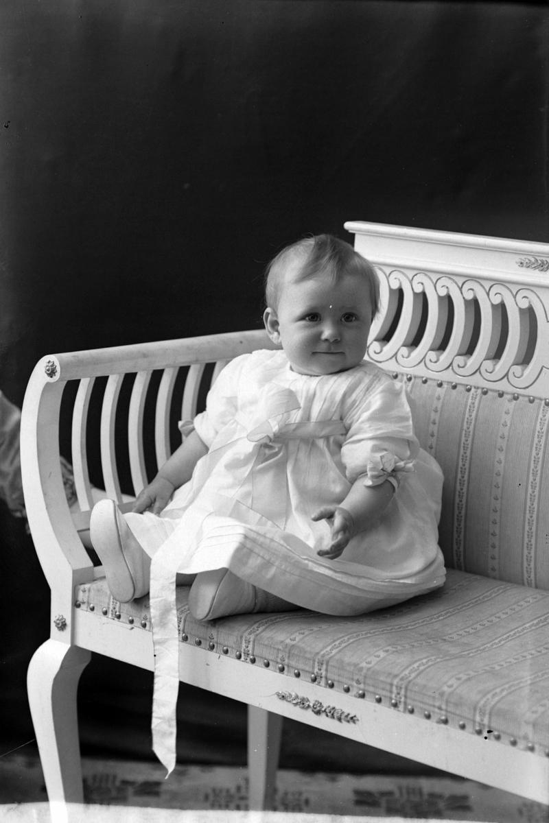 Studioportrett av et lite barn i en hvit kjole.