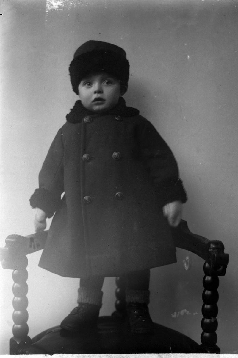 Studioportrett av et lite barn i kåpe.