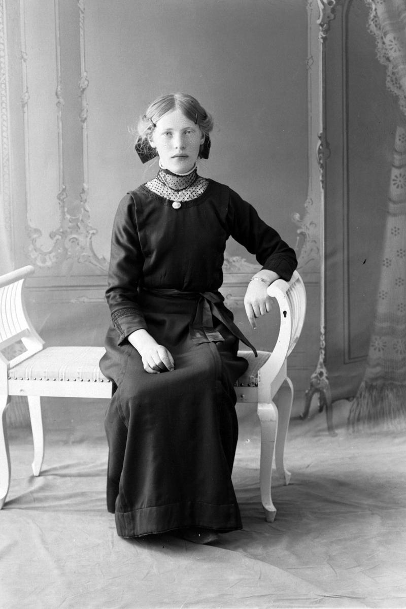 Studioportrett av en ung kvinne i en mørk kjole.