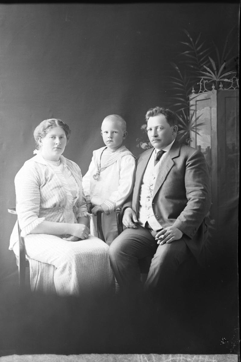 Studioportrett av en mann og kvinne med et barn mellom dem.