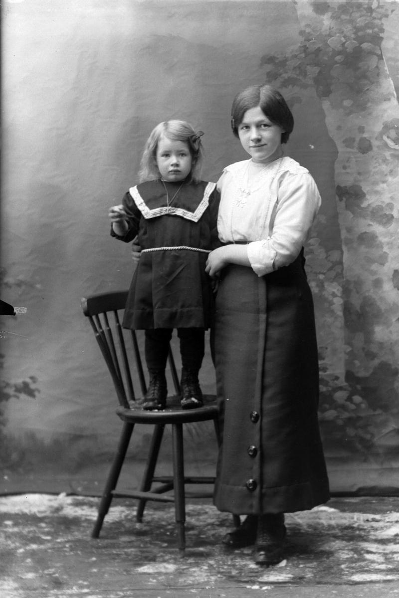 Studioportrett av en kvinne med et barn ved siden av seg.