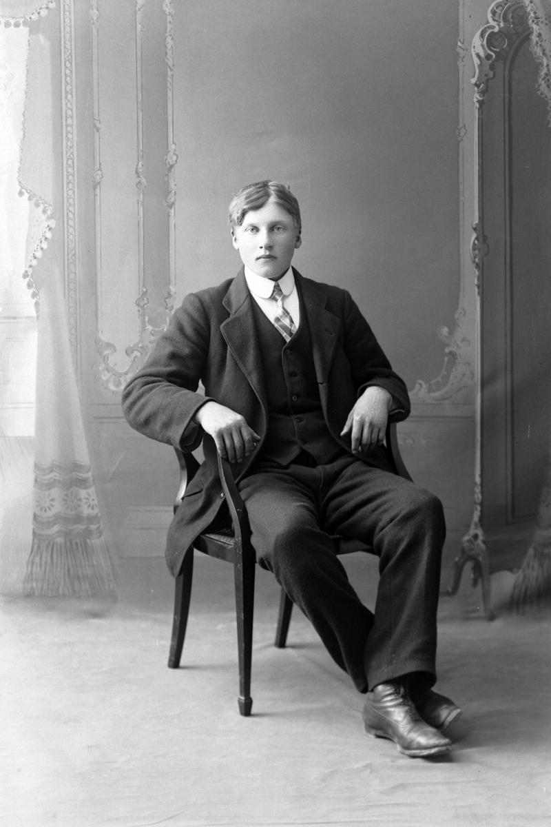 Studioportrett av ung mann i en stol.