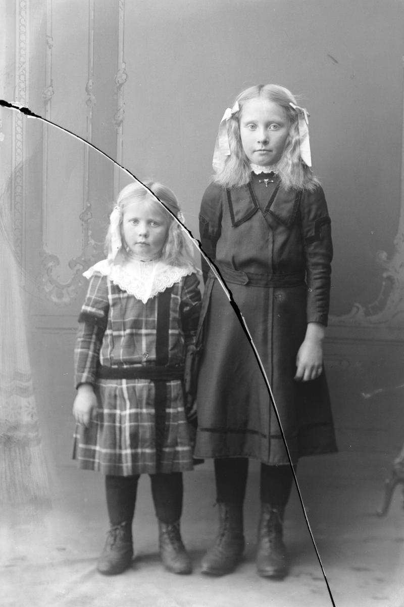 Studioportrett av to jenter i helfigur.