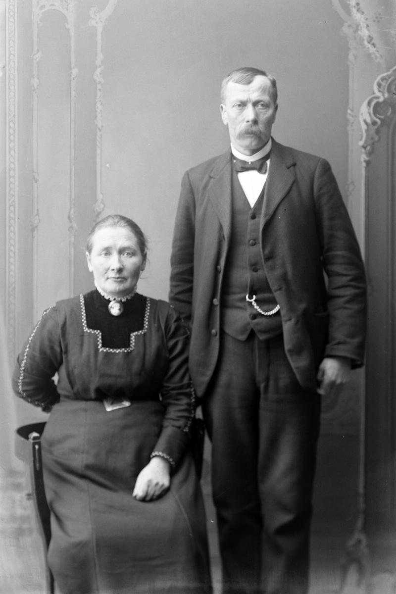 Studioportrett av en kvinne som sitter ved siden av en stående mann.