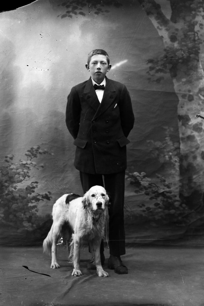 Studioportrett i helfigur av en gutt og en hund.