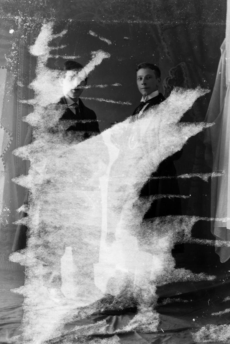 Studioportrett av to menn i helfigur. Bildet er delvis ødelagt.