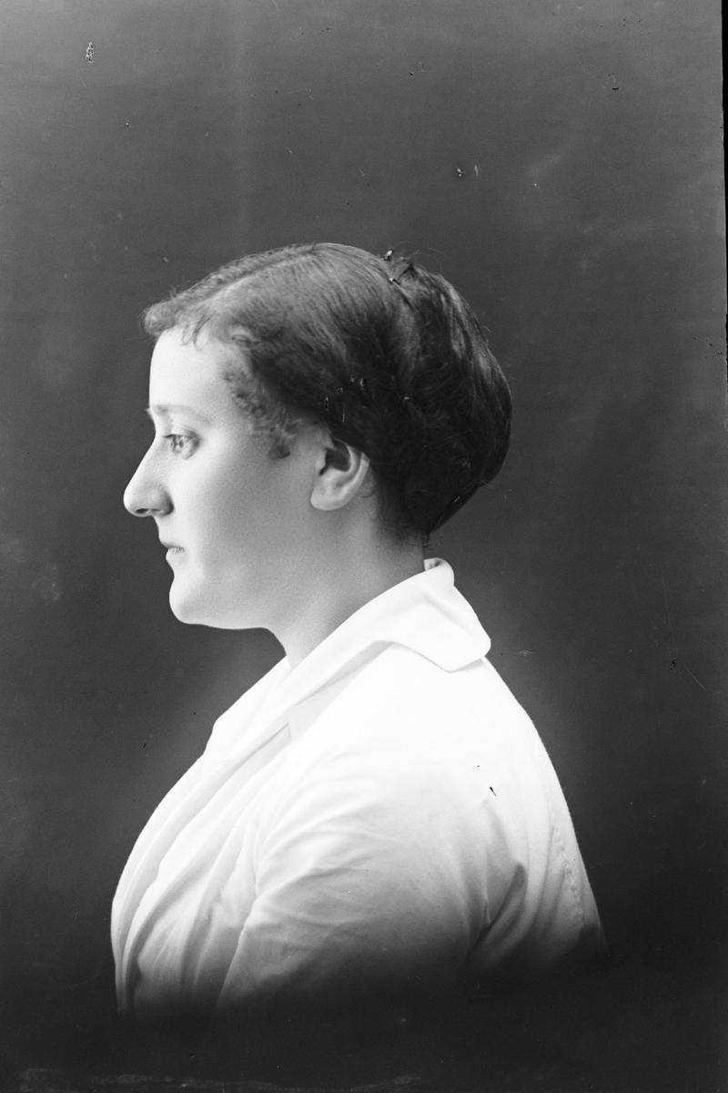 Studioportrett av en kvinne sett i profil.