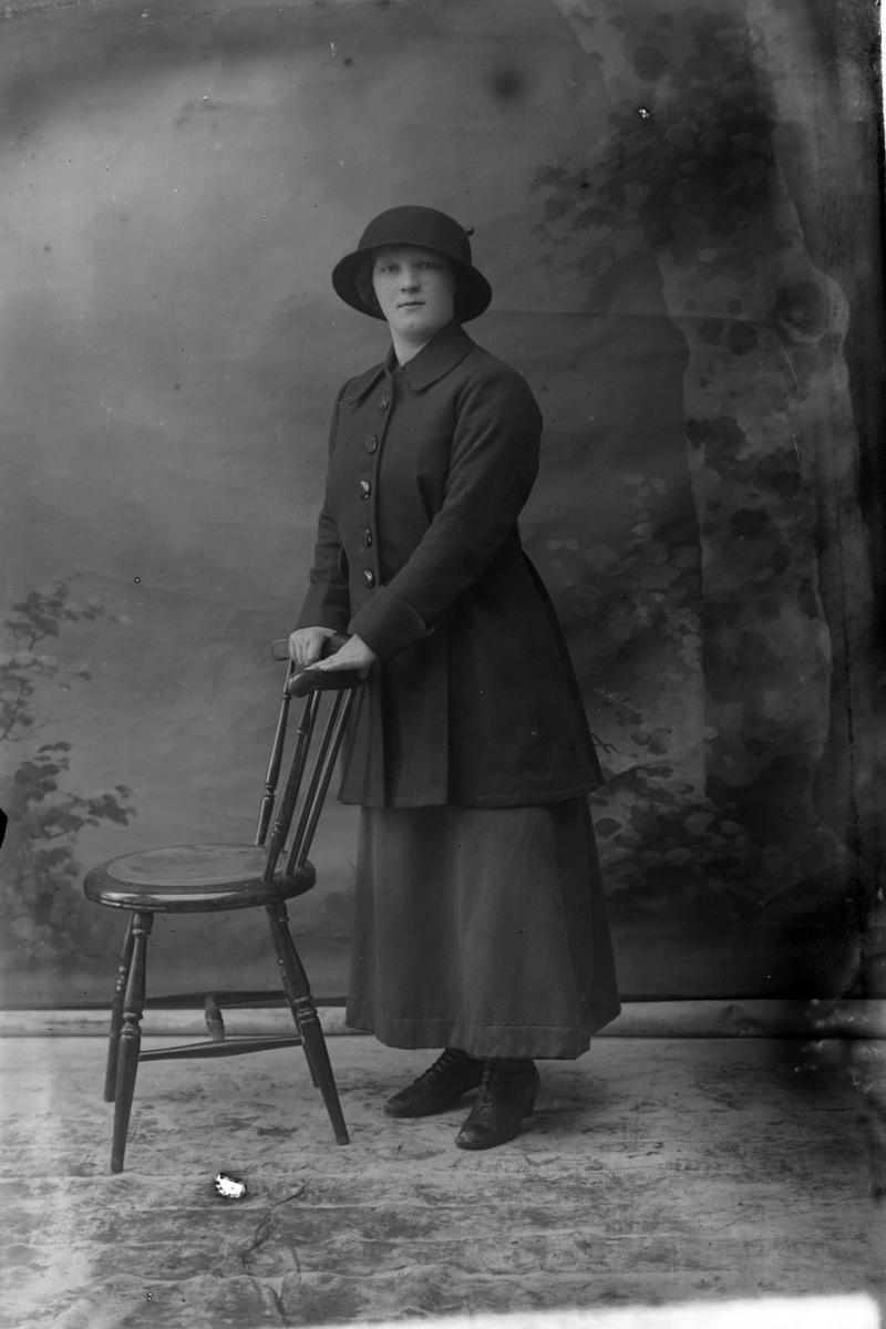 Studioportrett av en kvinne med begge hendene på en stolrygg.