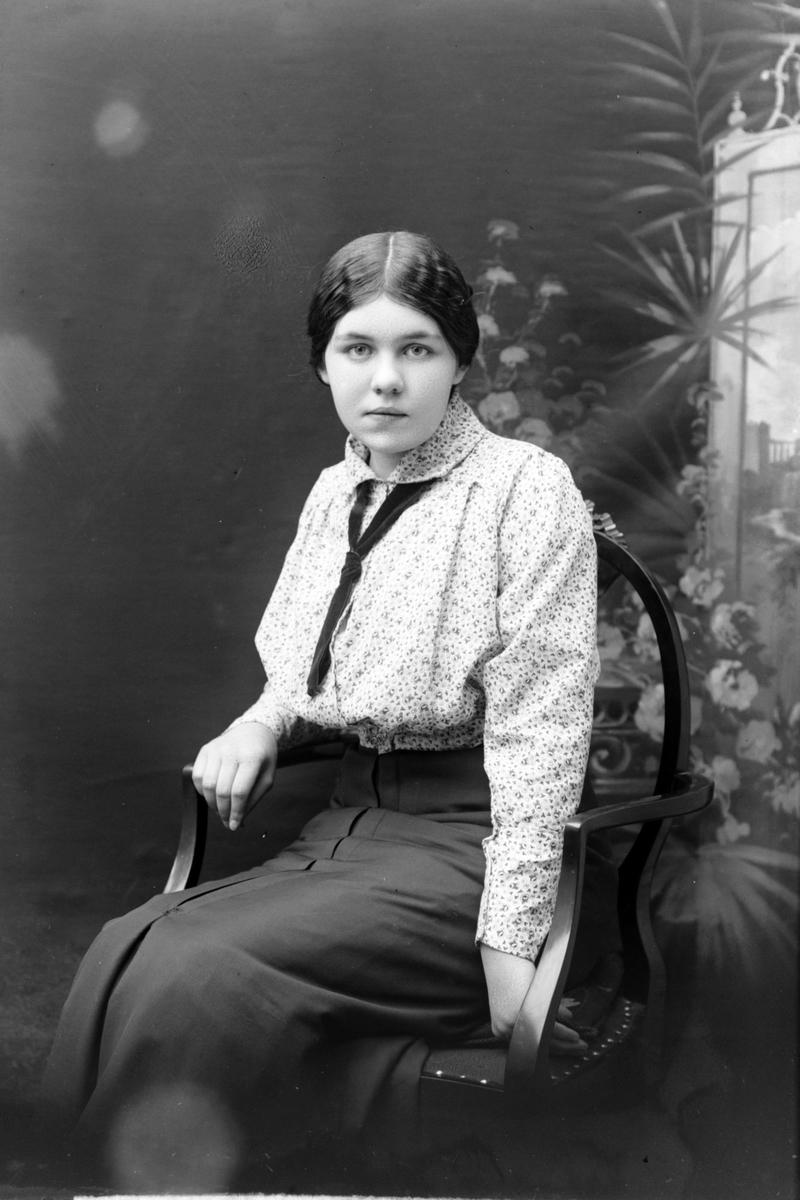 Studioportrett av en kvinne sittende på en stol.