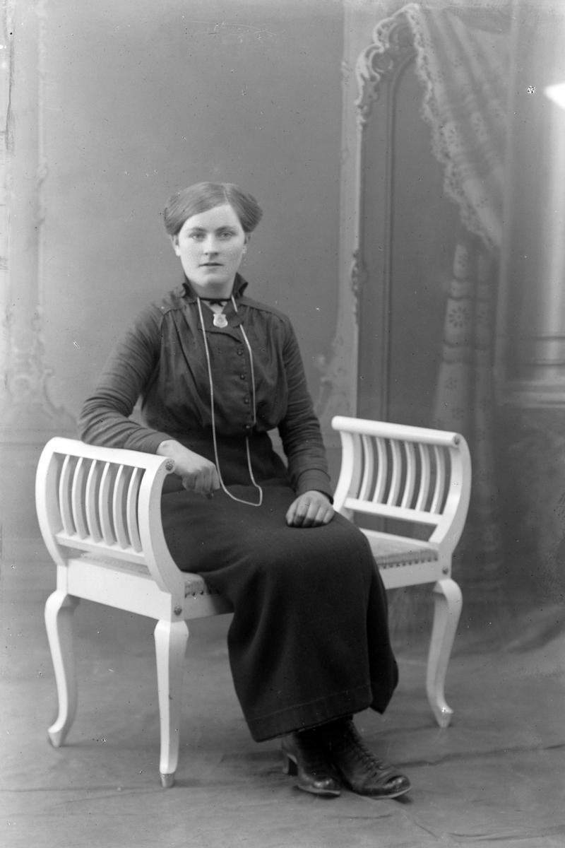 Studioportrett av en kvinne sittende på en benk.