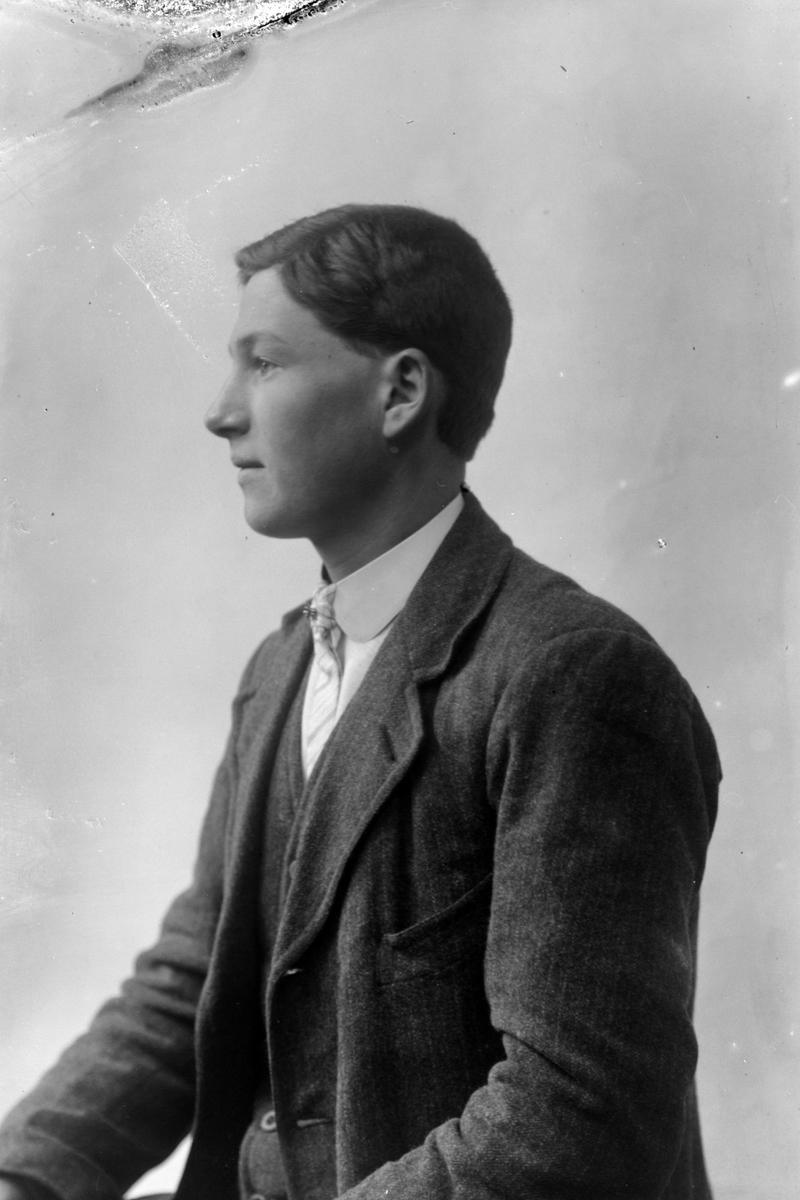 Studioportrett av en mann sett i profil.