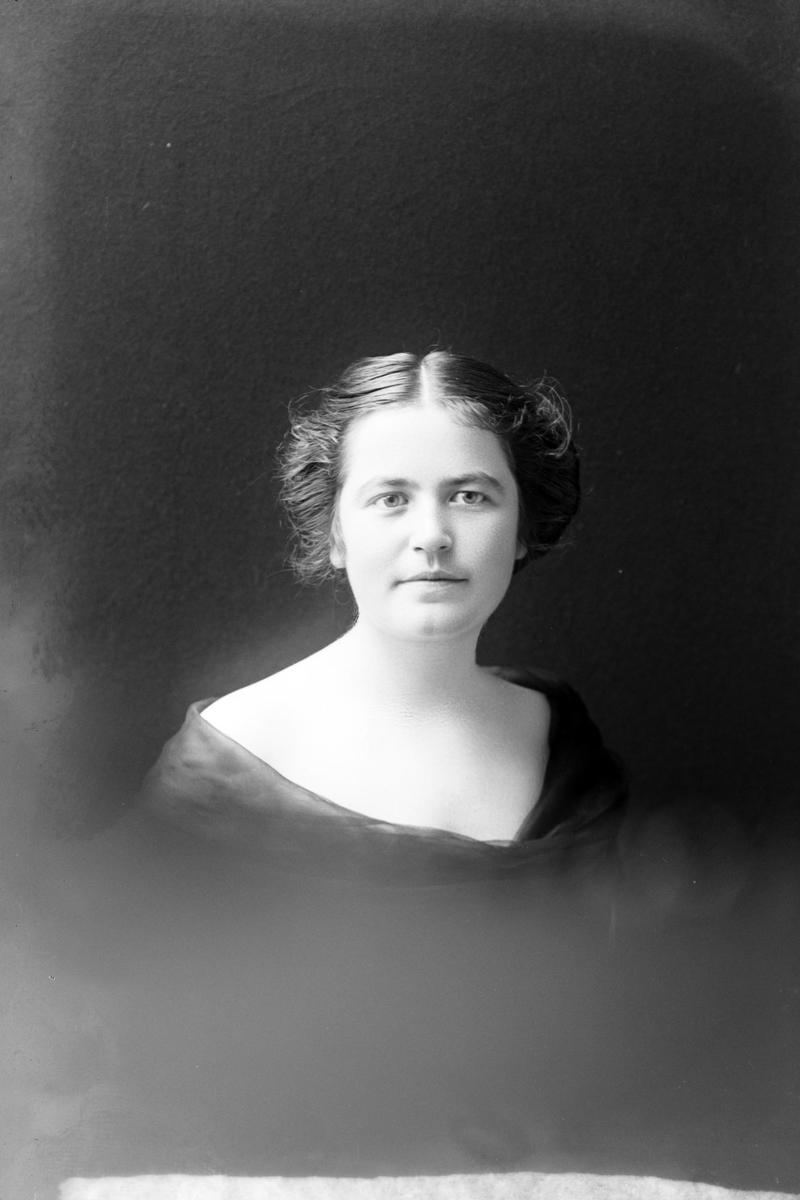 Studioportrett i halvfigur av Helga Elisabeth Daae.
