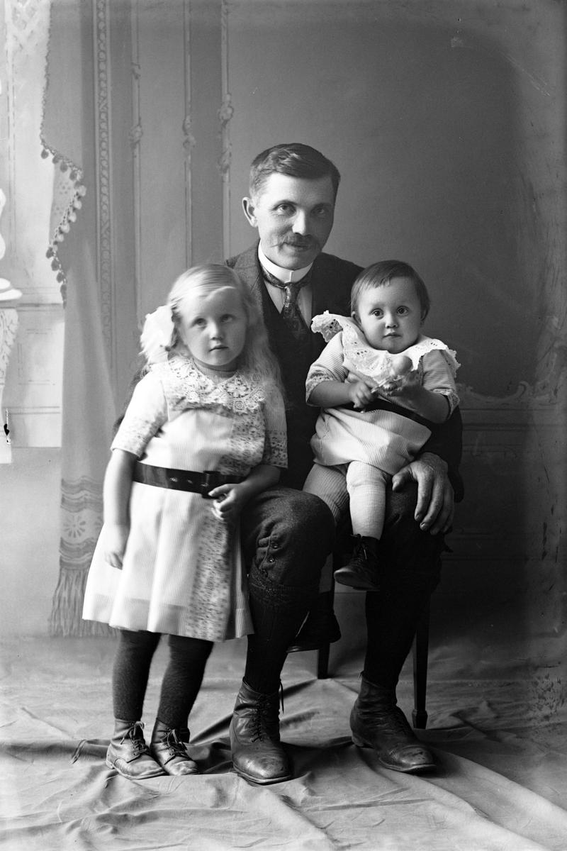 Studioportrett av en mann med to barn.