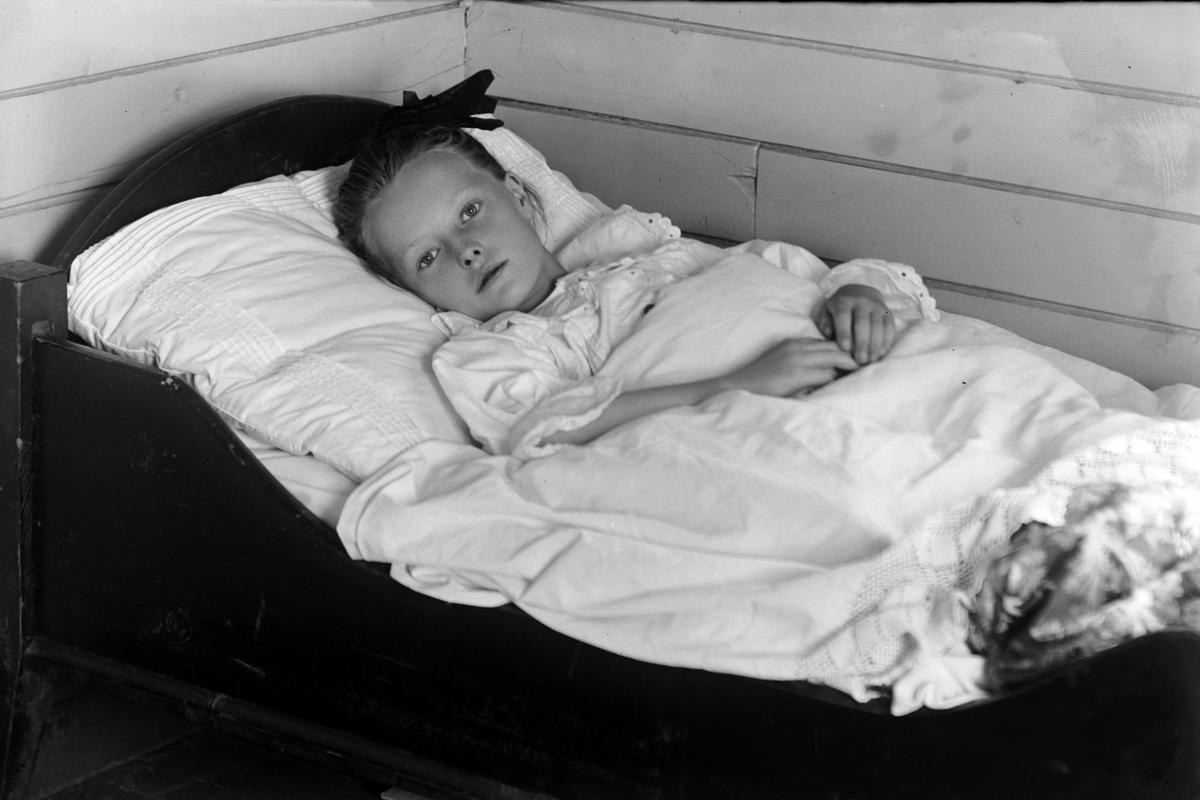 Portrett av en ung pike i seng.