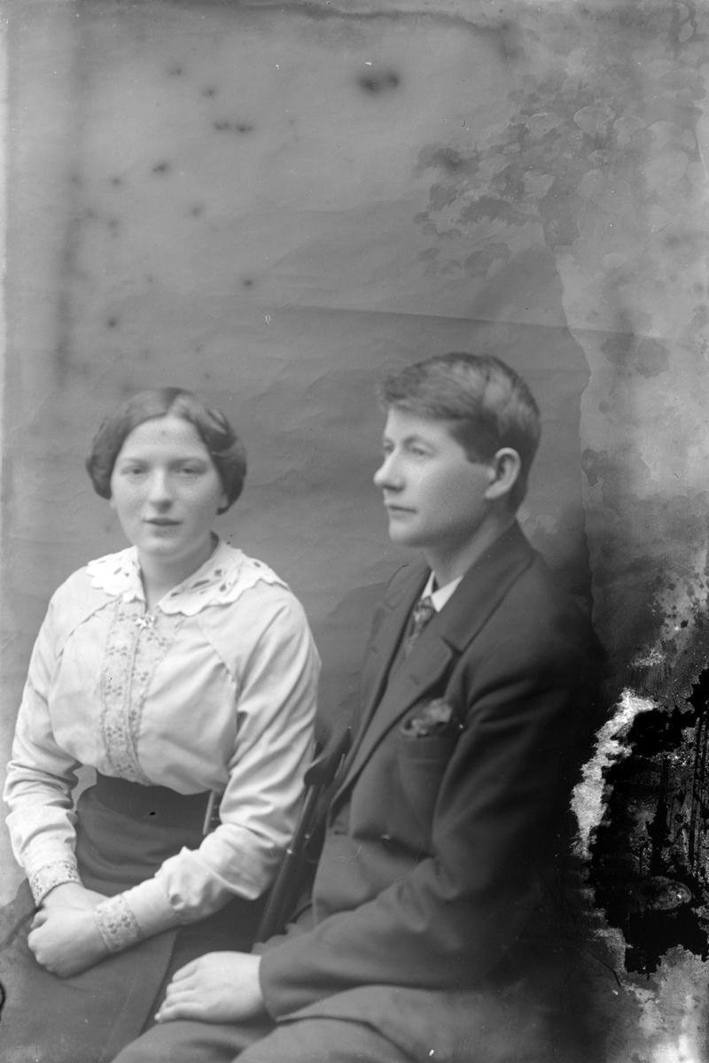 Studioportrett av en sittende mann og kvinne.